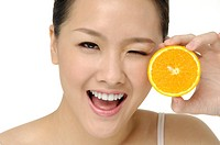 pretty asian woman with orange isolated on the white background