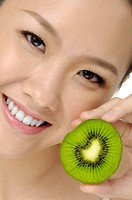 happy woman eating slice fresh ripe kiwi