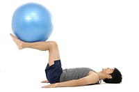 Side profile of a young man exercising with a fitness ball