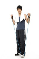 Young man doing fitness exercises with resistance rope