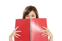 Female university student peeking from behind a spiral notebook