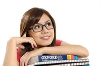 Female university student leaning on stack of books and thinking
