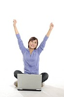 Female university student with her arms raised in front of a laptop