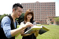 University students reading a book in a campus