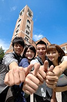 University students showing thumbs up sign in a campus