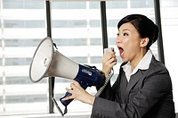 Businesswoman yelling through a megaphone in an office (thumbnail)