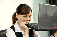 Businesswoman biting a laptop