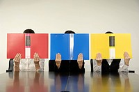 Businesswomen covering their faces with files