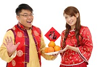 Couple holding Chinese new year couplets and oranges