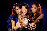 Female friends toasting with various drinks in a party