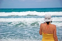 Woman looking out towards sea on beach wearing hat with waves crashing