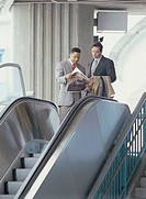 Two businessmen reading a newspaper on an escalator