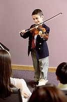 Boy playing a violin in front of an audience
