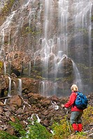 Rear view of a woman standing near a waterfall, Spray Falls, Mount Rainier National Park, Washington, USA