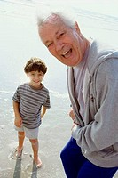 Portrait of a grandfather laughing with his grandson on the beach