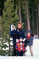 Portrait of parents with their son and daughter standing in snow