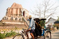 Side profile of a man driving a pedicab and guiding tourists in front of a temple, Chiang Mai Province, Thailand