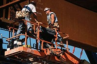 Low angle view of two steel workers bolting girders at a bridge construction site