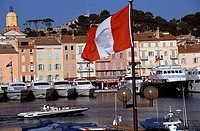 Flag in front of buildings, St. Tropez Harbor, French Riviera, Provence_Alpes_Cote d´Azur, France