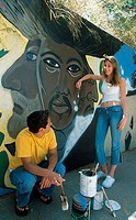 Young couple painting a mural on a wall