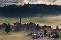 Village of Speiden in the Allgaeu and clearing autumn mist, Bavaria, Germany
