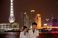 Young couple using mobile phones, Shanghai, China