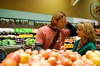 Young couple looking at each other and smiling in a supermarket