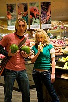 Young couple standing together and holding fruit in a supermarket