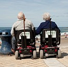 Rear view of an elderly couple husband and wife at the seaside sitting in powered mobility scooters, Aberystwyth Wales UK