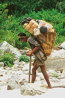 Nepali porter carrying large load on his back along a track on the banks of the Sunkosi river Nepal Asia