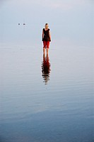Female standing in shallow water of German Wadden Sea, Juist, Lower Saxony, Germany