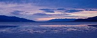 Cloudy winter sunset over temporary lake in flooded Badwater Basin, Death Valley national park, California