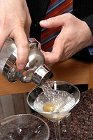 Man pouring a gin martini from a shaker into stemmed glasses with olives  St Paul Minnesota MN USA