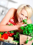 Blond woman smelling basil in kitchen