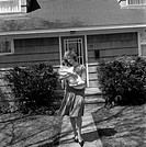 Mother carrying baby outside house