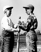 Vintage photograph of two boys wearing baseball caps, gripping baseball club