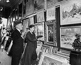 Side profile of a mature couple looking at paintings in a store