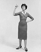 Mid adult woman standing with her hand on her hip and pointing upward