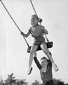 Boy pushing his sister on a swing