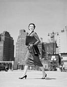 Cheerful businesswoman walking in downtown
