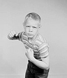 Studio portrait of boy clenching fists