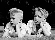 Twin boys lying on grass and looking away