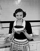 Happy young woman holding layer cake
