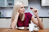 Blond young woman looking at pastry