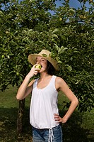 Young woman eating apple from tree