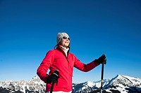 Smiling woman with ski poles in winter landscape, Tannheimer Tal, Tyrol, Austria