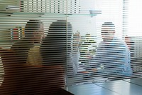 Meeting in office viewed through glass wall