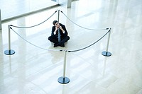 Businessman sitting on floor inside roped off area in lobby (thumbnail)