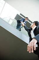 Businessman leaning over balcony, holding on to colleague's hand