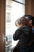 Toddler boy in father's arms, looking out window